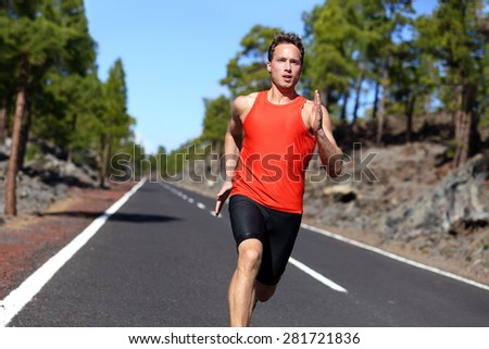 Sport sprinting young athlete handsome male training outdoors for marathon run. Fitness model in his twenties running on road in summer nature. - stock photo