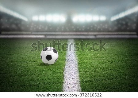 Sport stadium in light of spotlights with football ball in the center - stock photo