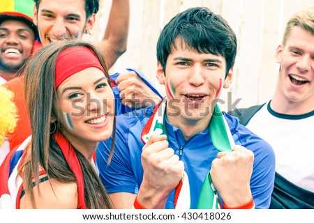 Sport supporter cheering at football stadium together with many multiracial fans - Young man at sportive event screaming at the moment of goal scored - Happiness and enthusiasm concept - Focus on male - stock photo