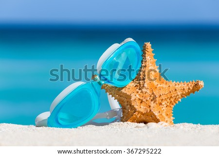 Sport swimming glasses and starfish on white sand against turquoise caribbean sea water. Tropical summer vacation concept - stock photo