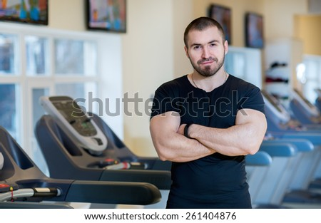 Sport training and confidence. Portrait of young handsome sports looking guy. Man is looking in the camera, treadmills on background - stock photo