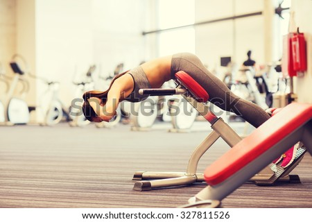 sport, training, fitness, lifestyle and people concept - young woman flexing back muscles on bench in gym - stock photo