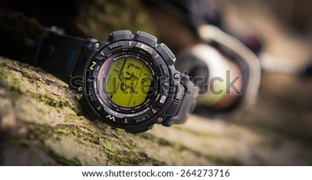 Sport watch on hand with empty screen on nature green background - stock photo