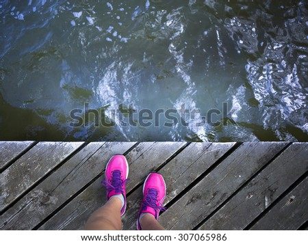 Sport woman's legs with pink sneakers relax on wooden pier near sea - stock photo