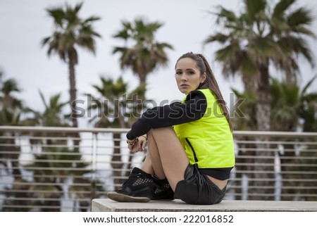 Sport woman sitting under palms