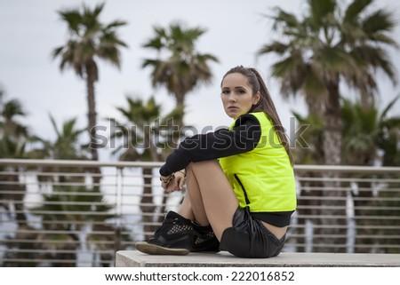 Sport woman sitting under palms - stock photo