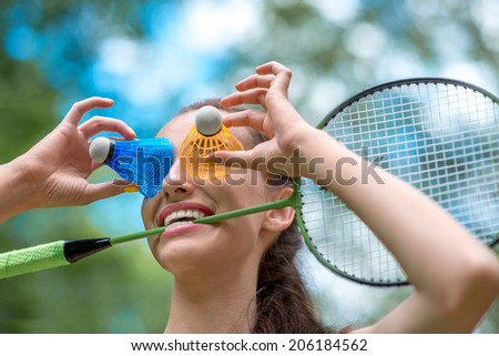 Sport woman with badminton racket and shuttlecock near her eyes in the park - stock photo