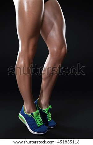 Sport womens legs isolated on dark background - stock photo