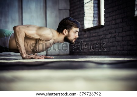 Sport. Young athletic man doing push-ups. Muscular and strong guy exercising. - stock photo