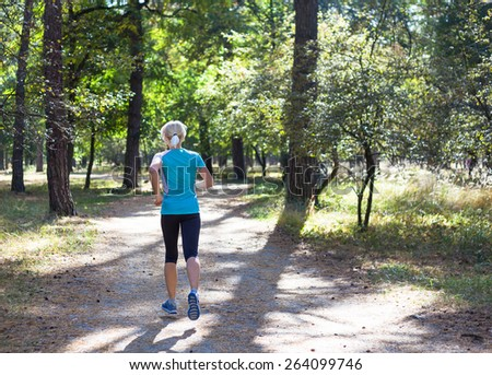 Sport young woman running in morning forest - stock photo