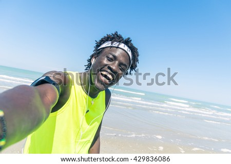 Sportive black man taking selfie at the beach - stock photo