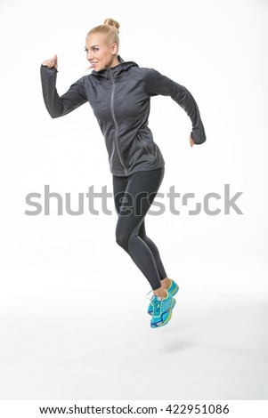 Sportive blonde girl in the sportswear runs on the white background in the studio. She wears cyan-yellow sneakers, black-gray pants and gray hoody. Her feet are off the floor. She looks forward with a