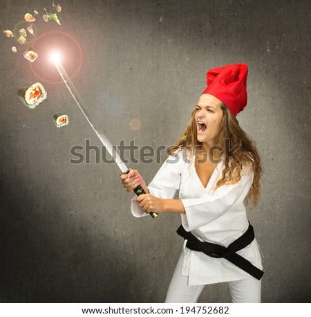 sportive chef made sushi with samurai sword - stock photo
