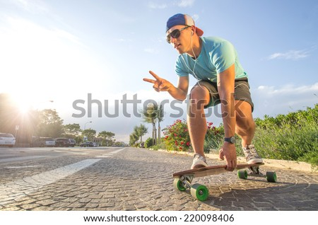 Sportive cool an on a skateboard  - cool street skateboarder in a urban setting - fashion,sport,lifestyle concept - stock photo