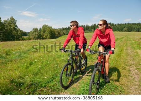 Sportive couple riding mountain bike in spring meadow on a sunny day