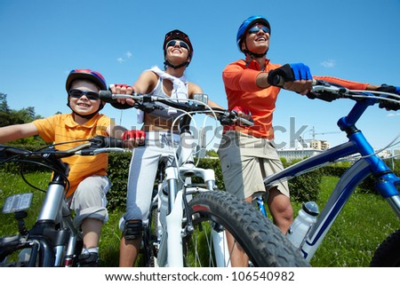 Sportive family keeping fit cycling on a clear summer day