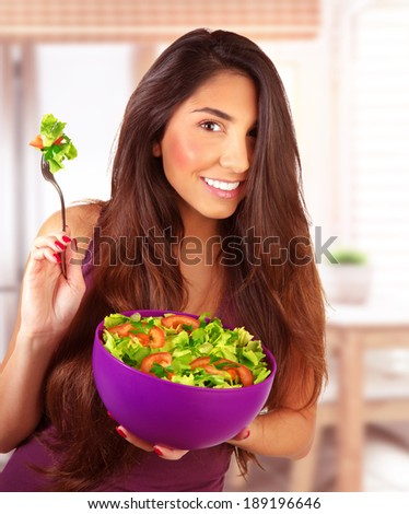 Sportive girl eating fresh vegetarian salad at home in the kitchen, loss weight, healthy nutrition, body care and beauty concept - stock photo
