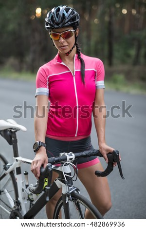 Sportive girl stands with a bike on the road on the blurry background of nature. She wears a pink sports jacket, black-pink shorts, sunglasses, a black helmet and a stopwatch. Vertical.