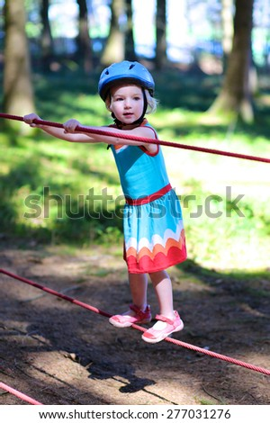 Sportive kid playing outdoors. Happy child, healthy toddler preschool age girl enjoying activity in a climbing adventure park on a summer day. - stock photo