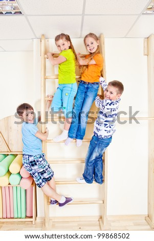 Sportive kids climbing on wall bars - stock photo