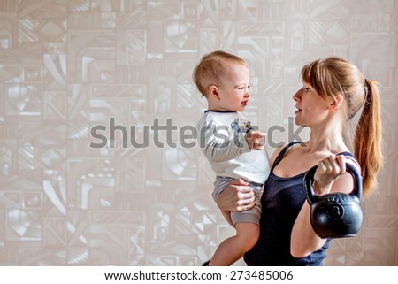 Sportive laughing mother and baby and kettlebell in hands. Motherhood is not a cause to let oneself go - stock photo