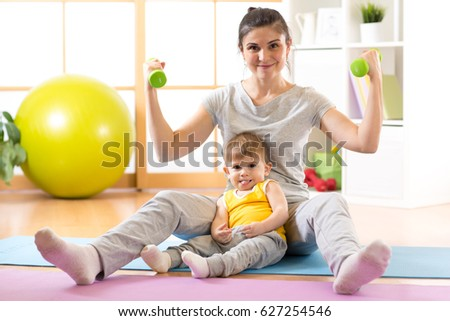Sportive laughing mother with baby boy and dumbbells in hands. Motherhood is not a cause to let oneself go.