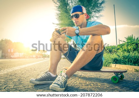 Sportive man at sunset listening music and looking at phone - stock photo