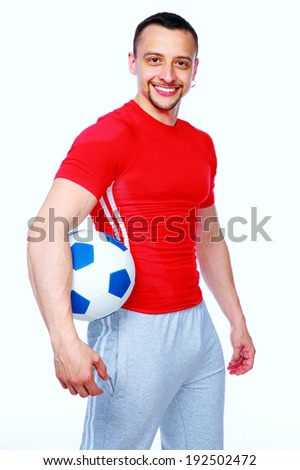 Sportive man holding soccer ball over white background - stock photo