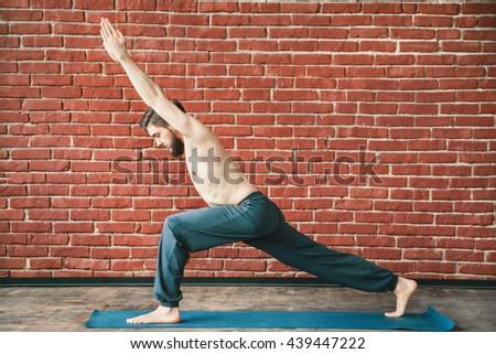 Sportive man with dark hair and beard wearing trousers doing yoga warrior position on blue matt at wall background, copy space, portrait, virabhadrasana. - stock photo
