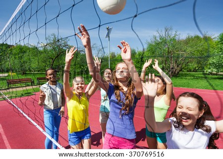 Sportive teenagers are playing volleyball together - stock photo