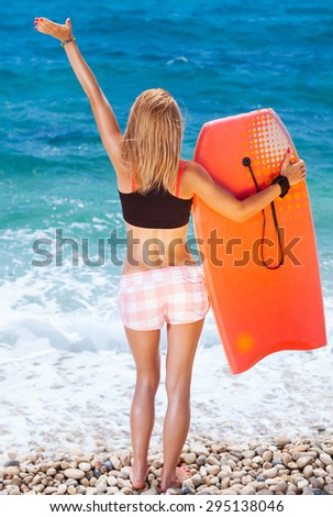 Sportive woman on the beach, slim girl standing back side and enjoying beautiful sea view with surfboard in hand and another hand raised up, enjoying active summer vacation - stock photo