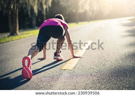Sportive woman working out outdoors. Young lady doing exercises and ready to start running. Health and sport concept.  - stock photo