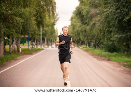Sportive young man runner jogging at great speed on a road
