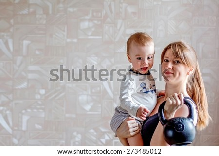 Sportive young redheaded mother with baby and kettlebell in hands. Motherhood is not a cause to let oneself go - stock photo