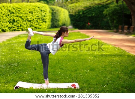 Sportive young woman stretching, doing exercises balancing in yoga pose - stock photo
