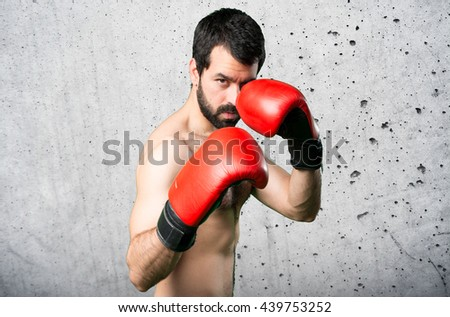 Sportman with boxing gloves over grey background