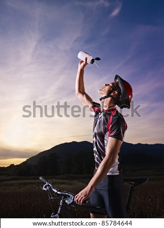 sports activity: young adult cyclist on mountain bike spilling water on face from bottle. Vertical shape, side view, copy space - stock photo