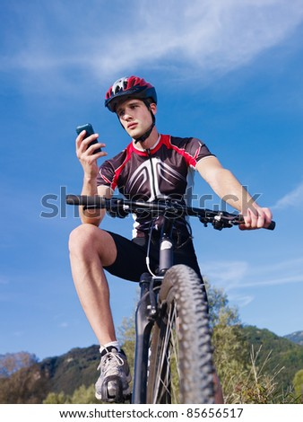 sports activity: young adult cyclist riding mountain bike and text messaging on cellphone. Vertical shape, low angle view - stock photo