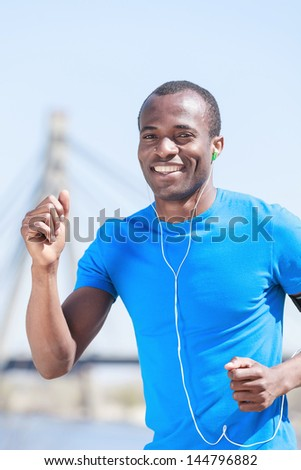 Sports and music. Young african descent men jogging and listening to the MP3 player - stock photo