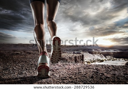 Sports background. Runner feet running on desert closeup on shoe.  - stock photo