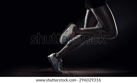 Sports background. Runner. Side view of a jogger legs isolated on black - stock photo