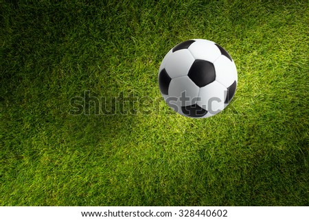 Sports background - soccer ball and green field, bright light from spotlight - stock photo