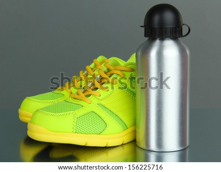 Sports bottle and sneakers on grey background