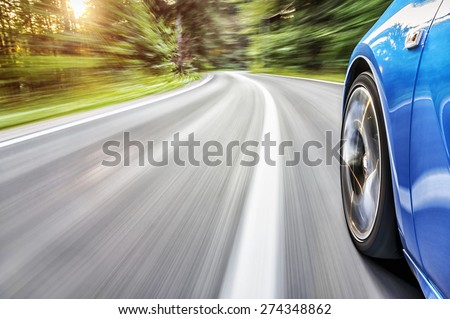 Sports car driving at the sunset - stock photo