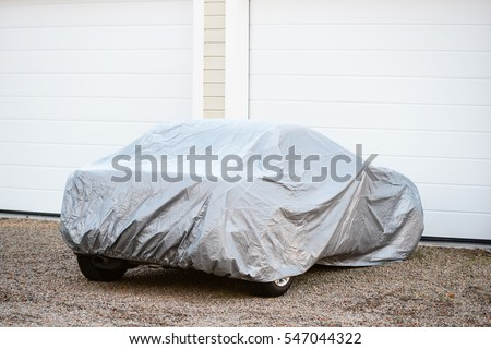 Sports car under silver colored cover outside a closed garage.