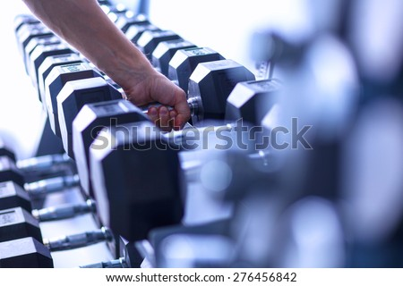 Sports dumbbells in modern sports club - stock photo