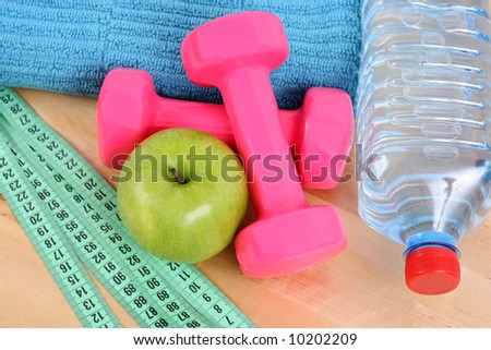 sports equipment - dumbbells water and green apple