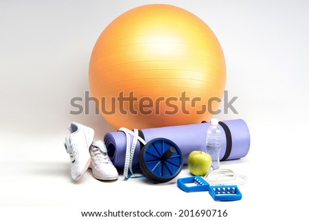 Sports equipment, Gym ball, yoga mat, abs roller, sneakers, green apple, measuring tape and water bottle closeup isolated on white - stock photo