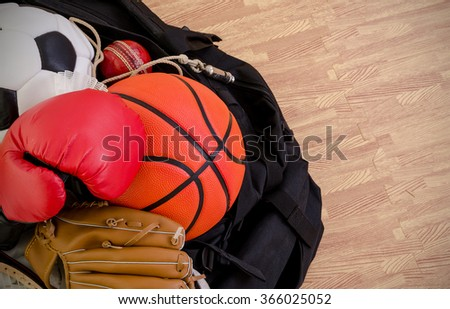 sports equipment in a holdall sports bag on a gym floor. football, baseball, cricket, basketball, boxing. with copy space. - stock photo