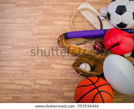 sports equipment on a gym floor, football, hockey, rugby, baseball, cricket, basketball, boxing, badminton and squash. - stock photo